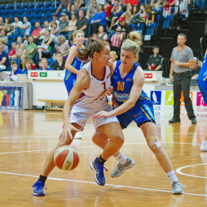 One player tries to take the ball from another in a women's basketball game in Australia.